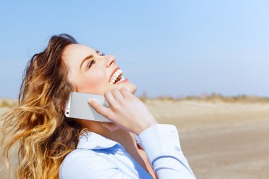 Happy woman laughing on the mobile phone on the seaside