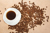 bílý šálek horké kávy, zrna na vyhození