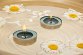 Photo Two burning candles, heads of camomiles in a dish with water