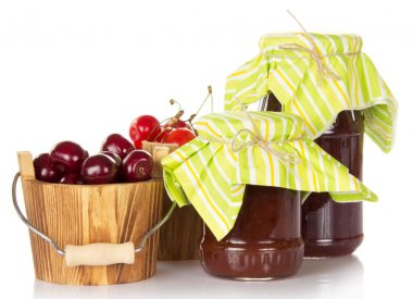 Different grades of sweet cherry in buckets and jars of jam isolated on white