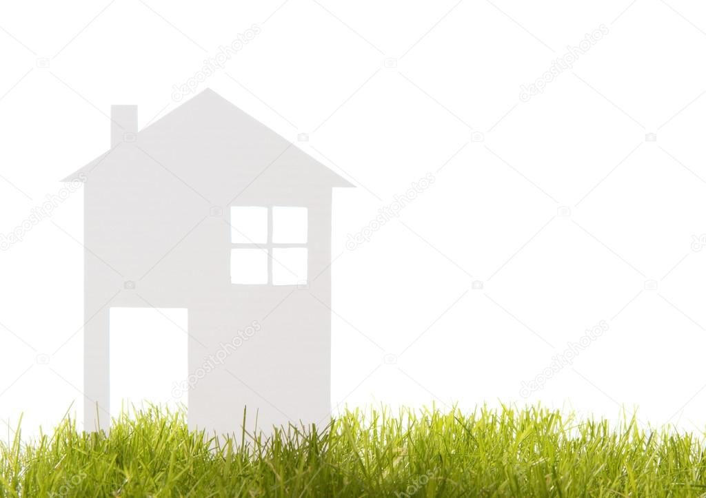 House cut out of paper on the grass