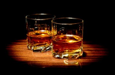 Two glasses of whiskey isolated on black