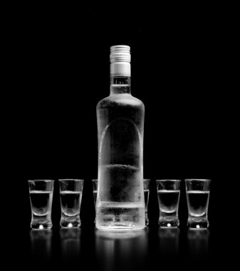 Bottle and glasses of vodka standing isolated on black background