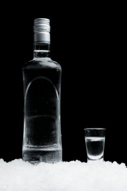 Bottle with glass of vodka standing on ice on black background