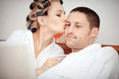Young couple working at home in bed