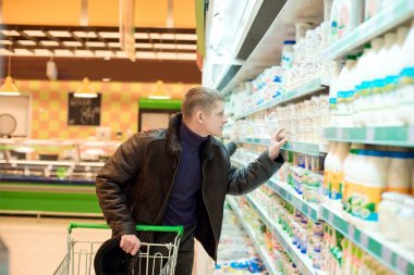 Man buys dairy products at the supermarket