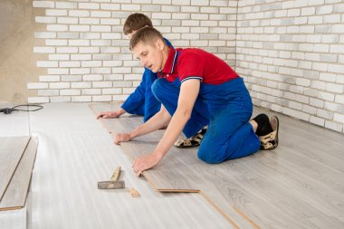 Young handsome men laid laminate floor covering, perform repairs