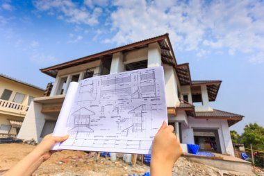 architecture drawings in hand on big house building