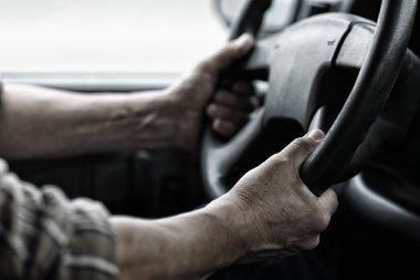 Worker hands on steering wheel