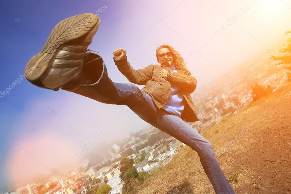 Woman fooling around doing high kick
