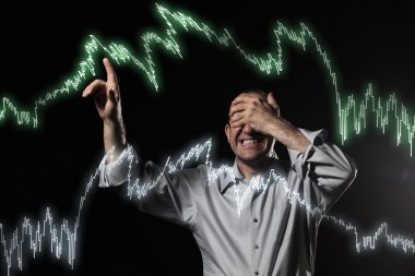 Scared trader pointing to stock market charts