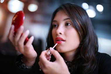 Beautiful young woman applying red lip gloss