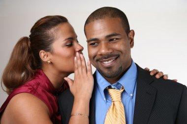 Woman wispering in husband's ear