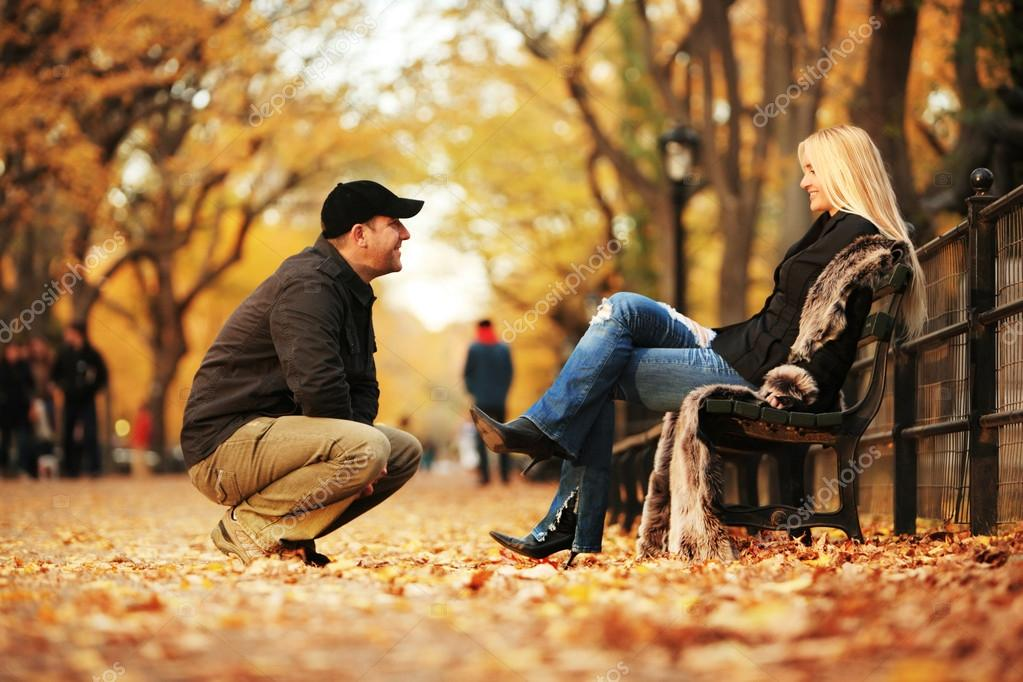 Man talking to hot blond woman in autumn park.