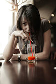 Fotografie tmavovláska pití červená šťáva
