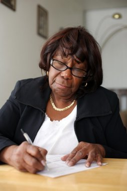 Elderly African American woman writing a letter.