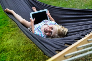 Child laying in hammock with tablet