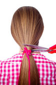 žena s dlouhými vlasy a stříhání nůžkami