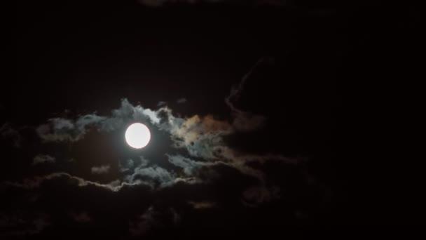 měsíc za pohybující se mraky