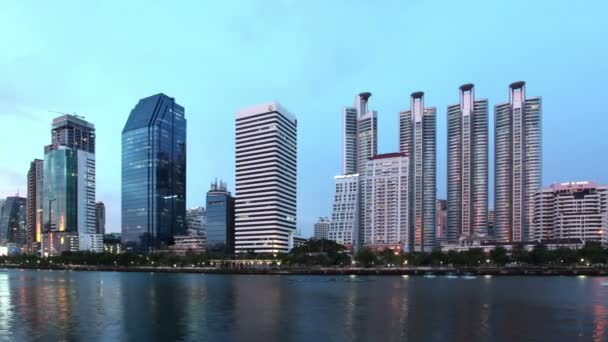 Time lapse - pan of Skyscraper, tall building, business tower, panorama scenery view at downtown at Sunset, evening to twilight night with reflection on lake or river, Bangkok capital city of Thailand