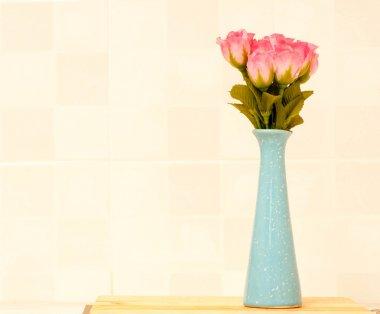 Pink rose on blue jar.