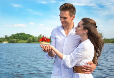 Guy hugs a girl near the water and holding her hand. Girl holdin