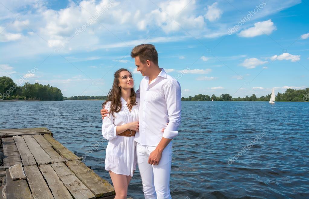 Guy hugs a girl on a wooden pier near the water.