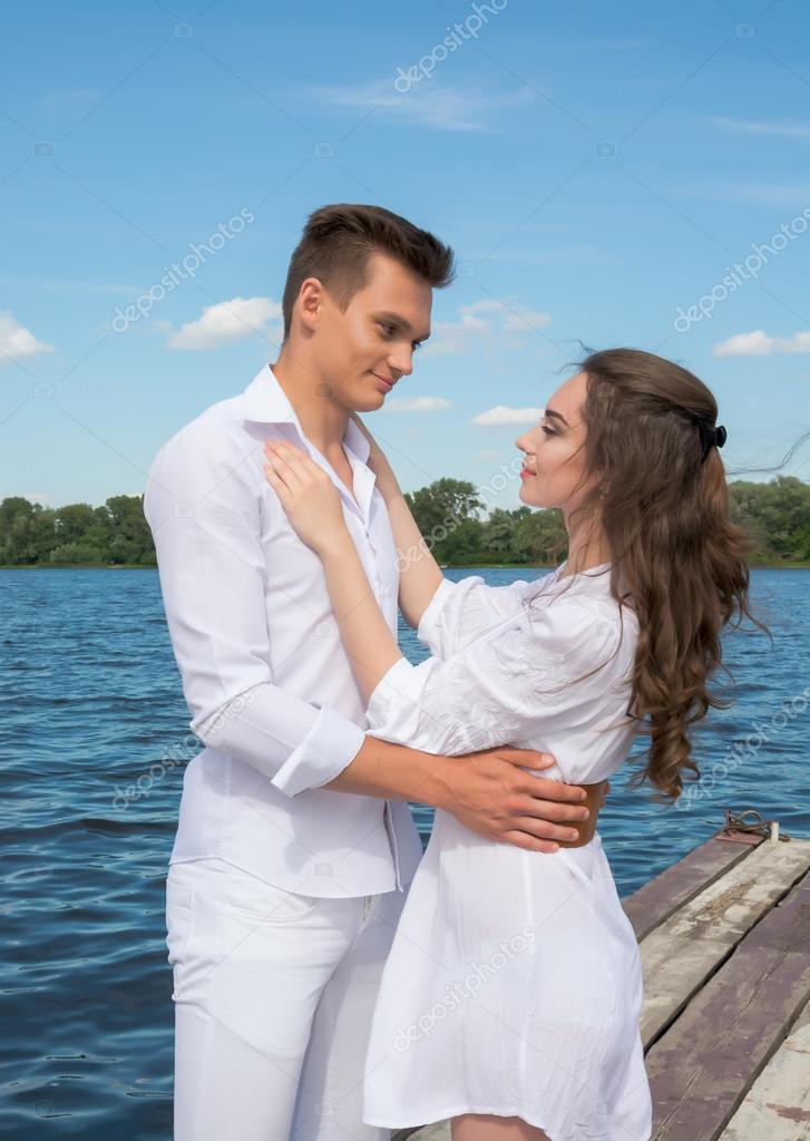 Guy hugs a girl near the water.