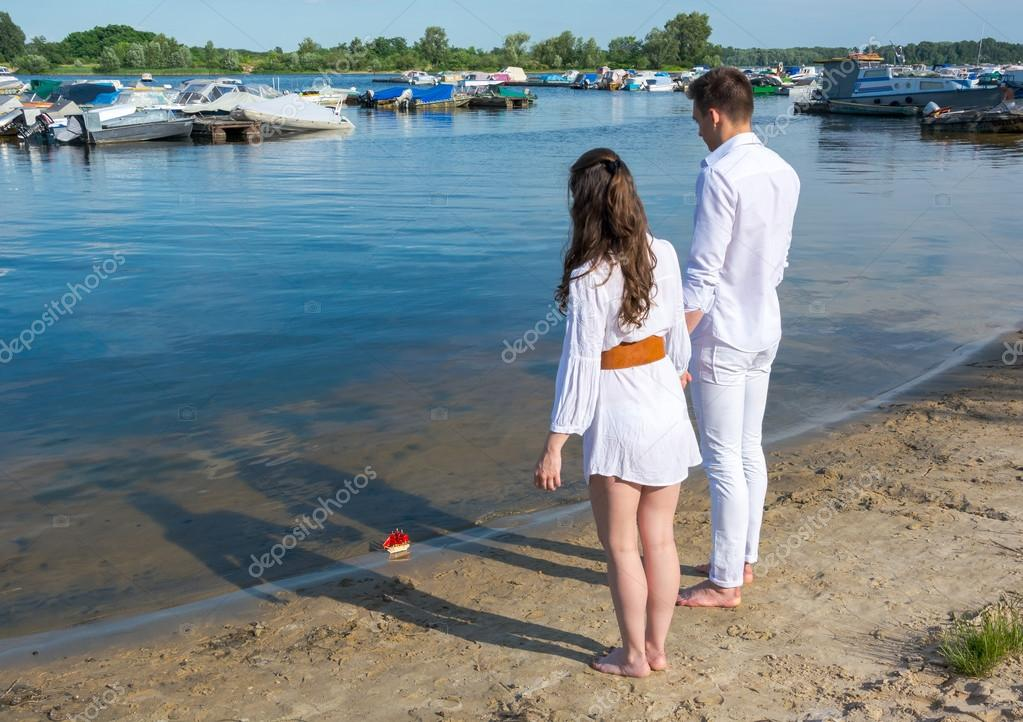 Man and woman standing on the river bank and see off toy boat wi