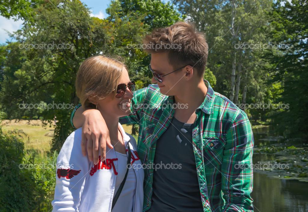 Man hugs a girl on the bridge in a park
