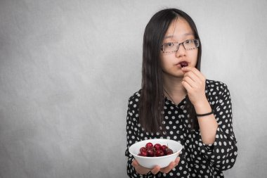 Girl eating a bowl of cherry
