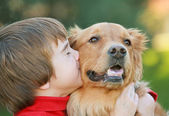 Fotografie Junge küsst Hund