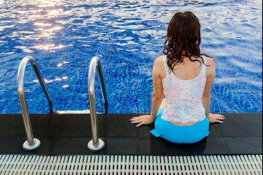 Rear view of a pretty woman sitting on the edge of blue swimming