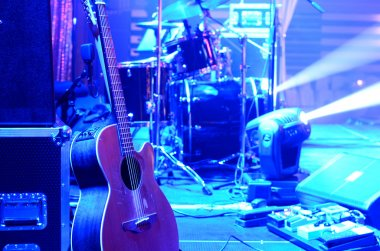 Acoustic guitar, drum kit, loudspeaker and other musical equipment on stage before concert. Neon light. Concept image. Night club, performance, music band, singing, profession, art, instrument