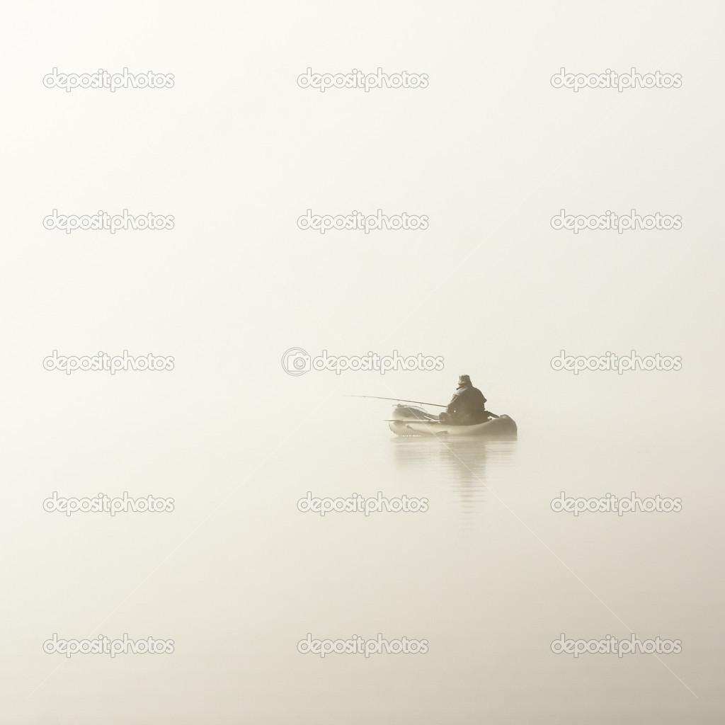 Fisherman in boat in fog