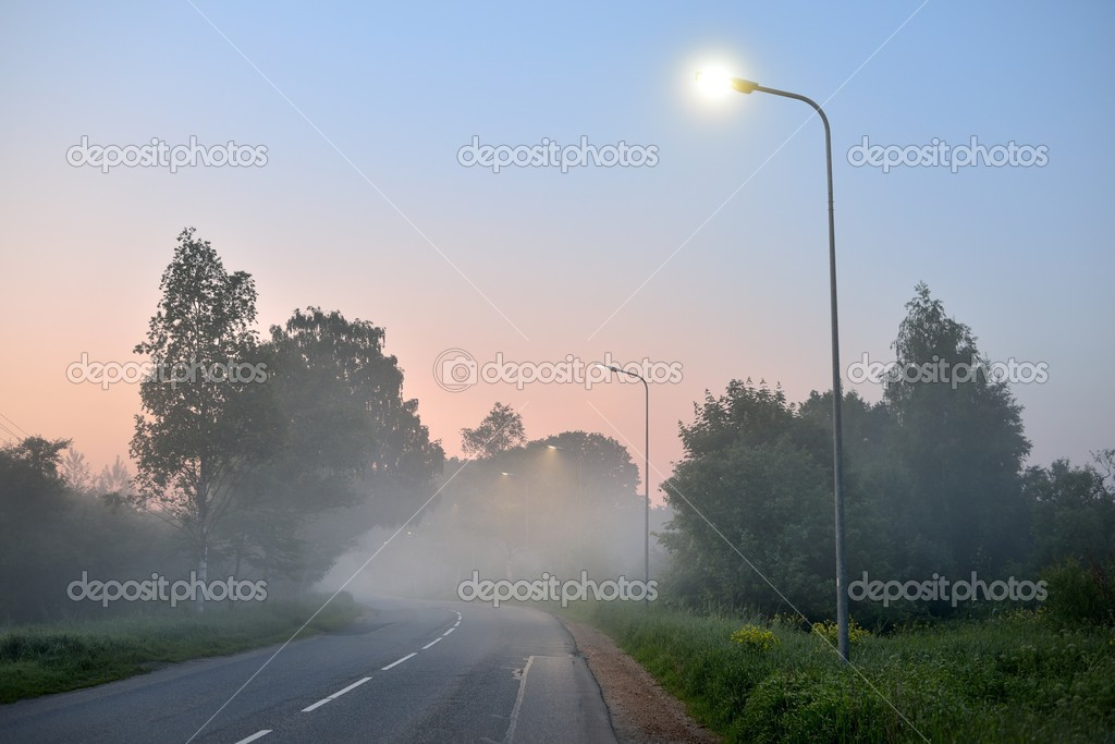 Road in rural area covered with morning fog