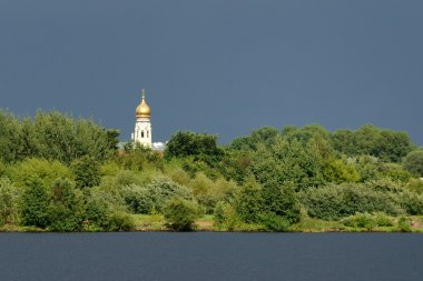 Old orthodox church with shiny cupola against stormy sky in Riga