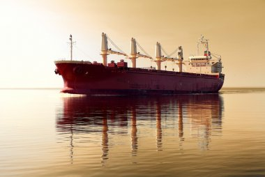 General cargo ship with cranes sailing in a still sea water. Golden sunset sky. Panoramic view. Freight transportation, nautical vessel, global communications, industry, carrying, logistics, commerce