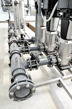 new shiny pipes and large pumps in industrial boiler room