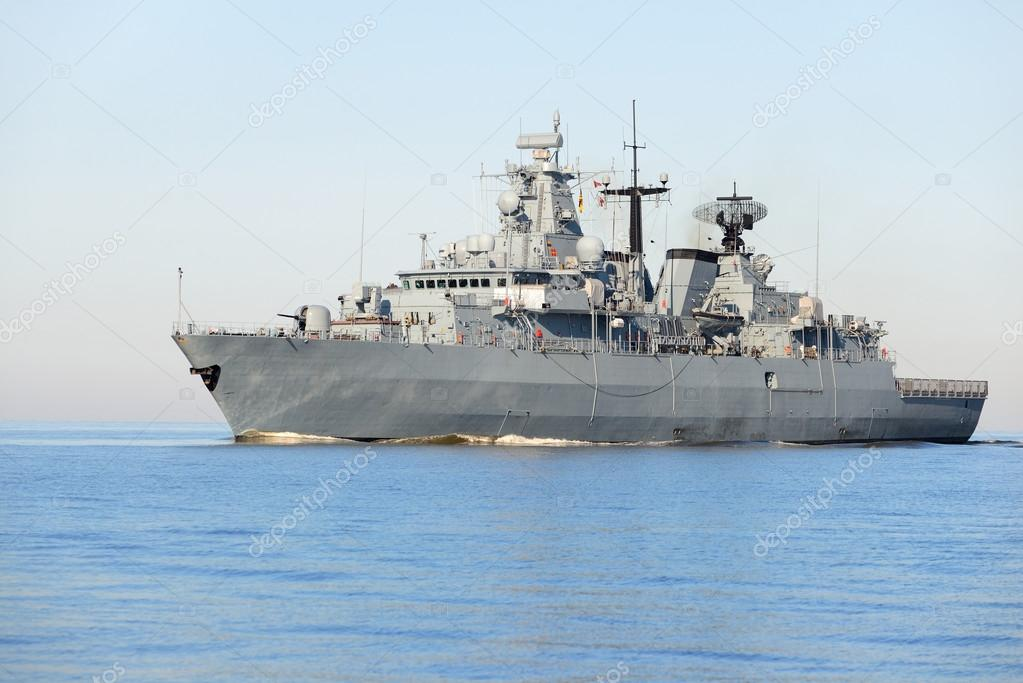 Grey modern warship sailing in still water