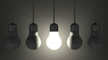 Glowing light bulb among dead ones in lamp sockets hanging on gray