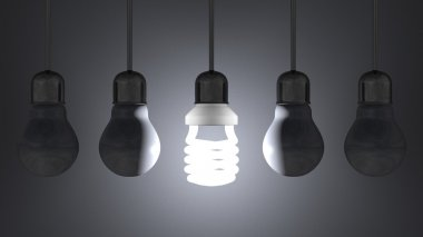 Glowing spiral light bulb among dead tungsten ones hanging on gray