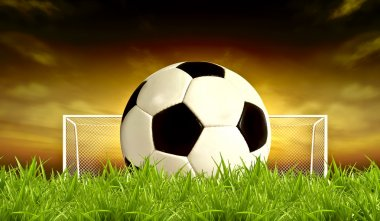 Soccer ball on green sunset Background