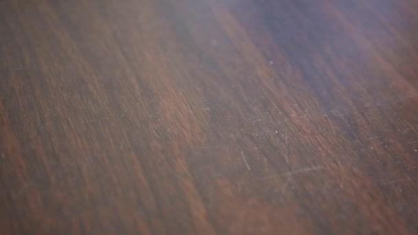 Mano bianca schiuma spray sulla tabella di legno