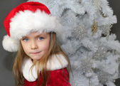 Fotografie Mädchen in rot gekleidet als Weihnachtsmann mit Weihnachtsbaum
