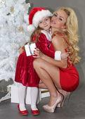 Fotografie Mutter und Tochter mit Weihnachtsgeschenke am Weihnachtsbaum