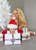 Fotografie Mutter und Tochter mit Weihnachtsgeschenken am Weihnachtsbaum