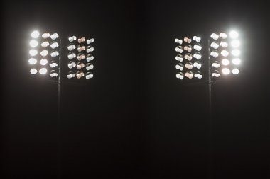 Stadium lights against dark night sky background