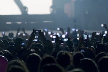 People taking photographs with touch smart phone during a music