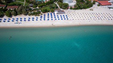Top view of beach with tourists, sunbeds and umbrellas at a luxu